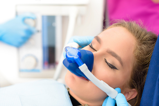 Woman with mask on her face receiving nitrous oxide sedation at dentist